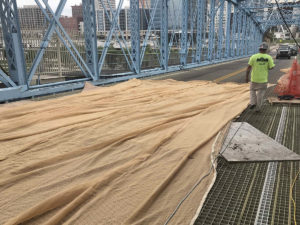 Construction on Roebling Bridge, netting being prepared
