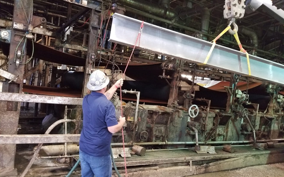 Worker maneuvers steel beam as part of Cincinnati Paperboard repairs