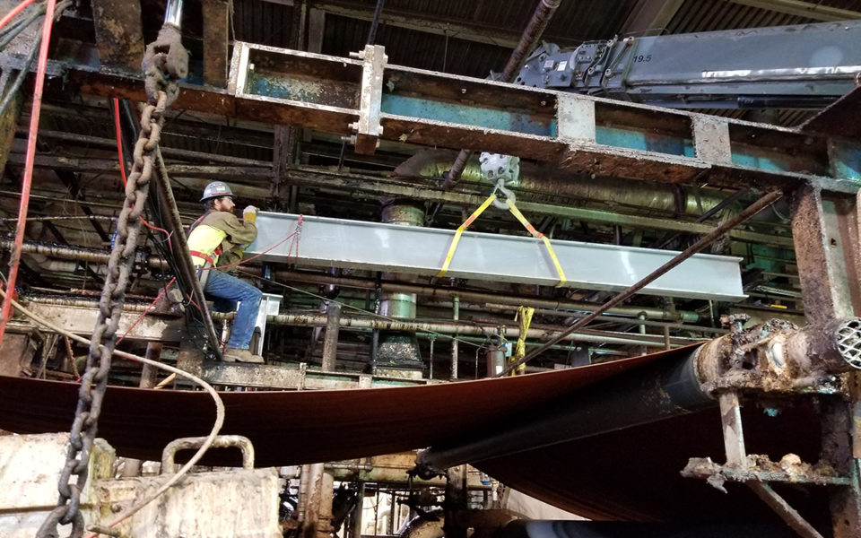 worked carefully maneuvers steel beam over active machinery as part of Cincinnati Paperboard repairs